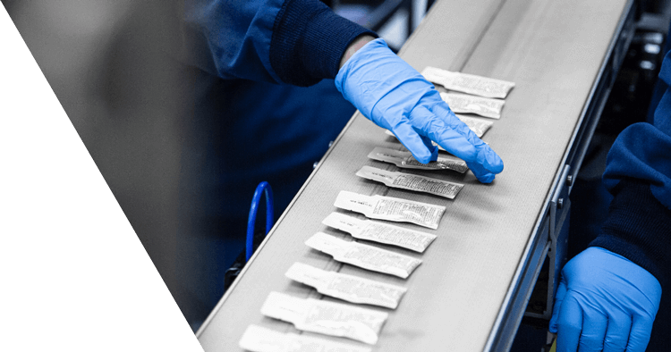Gloved assembly line worker examining squeeze pouches cropped