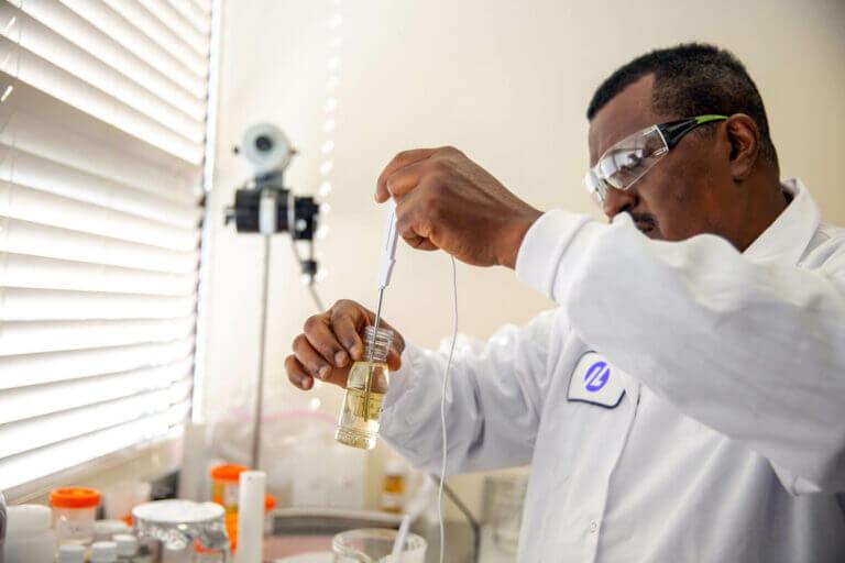 Man in lab jacket scrutinizing a beaker of liquid